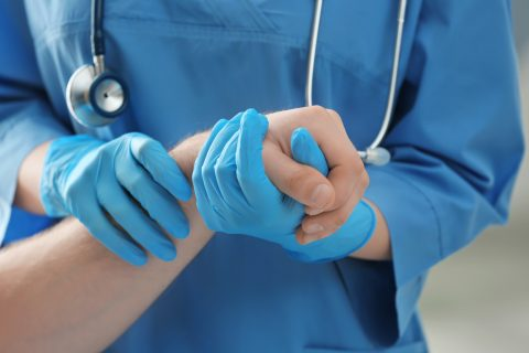 Medical assistant examining patient's arm in clinic, closeup